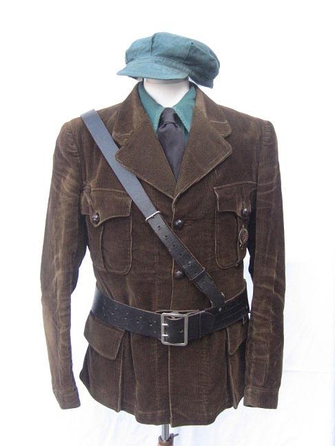 groen DMO-hemd met bruin-groene ribfluwelen jas. Het hoofddeksel is gemaakt van dezelfde stof als het hemd.